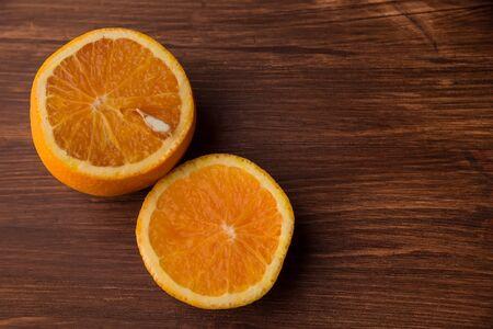 Orange on a wooden table. Juicy orange on a dark table.
