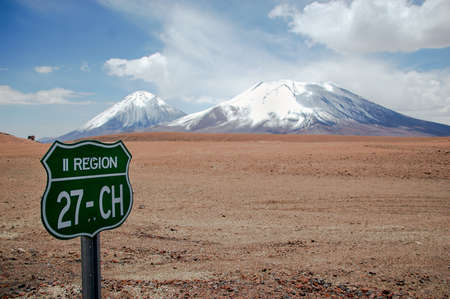 Landscape of an arid grassland with a snow mountains range in the background. Highway green sign on the left in a road from Chile. Field and mountain with blue sky Imagens
