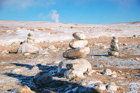 Stacked stone in National Reserve in Bolivia. Geothermal zone in high altitude. Steam rising from geysers. Snow landscape with blue sky