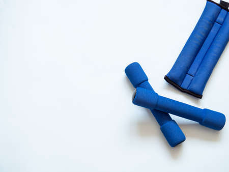Two blue small dumbbells and one ankle weight for strength training in white background. Copy space for text. Weightlifting and healthy lifestyle concept