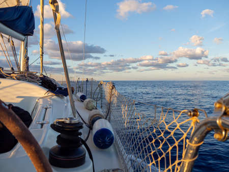 Starboard of a sailboat in the Mediterranean sea during sunset hour. Vacation, summer and adventure concept. Calm ocean while sailing.
