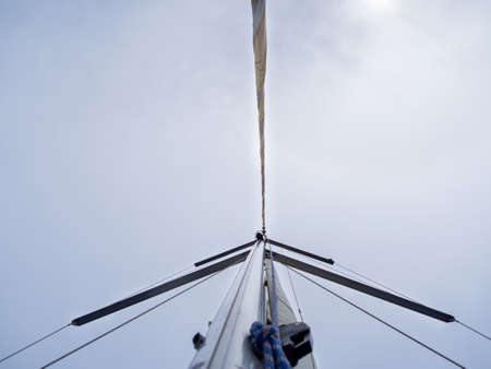 Mast of a sailboat in the Mediterranean sea with mainsail folded.