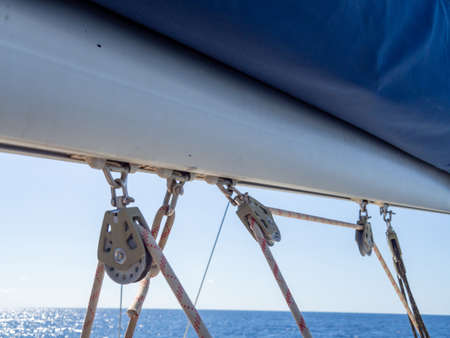 Close up of sailboat or yacht equipment. Boat pulleys with ropes on the mast. Ship details.