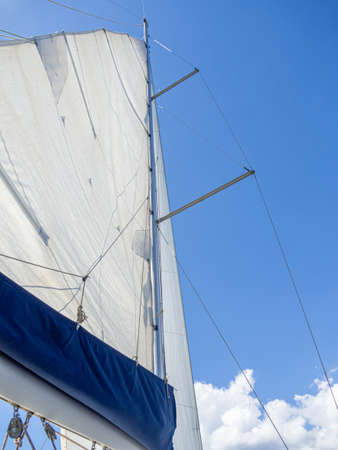 Sailboat mast in the mediterranean sea with blue sky. Vacation, summer and adventure concept. Mainsail unfold in the wind.