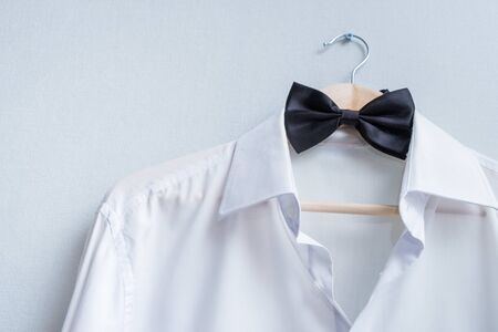 white mens shirt and black bow tie on a hanger
