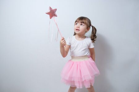 smiling little girl child holding a magic wand in his hand