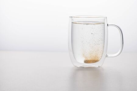 glass thermo mug of water-soluble effervescent orange tablet on a white table