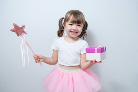 little girl child holds a gift box in one hand and a magic wand in the other Stock Photo