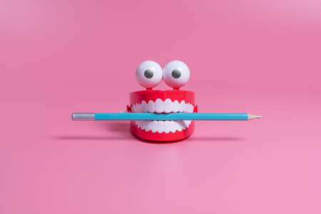 A plastic toy in the form of red jaws with white teeth and eyes holds a pencil between its teeth. Copywriting concept