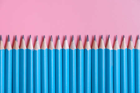 sharpened blue pencils for sketching or drawing on a pink background with space for text in a straight line. Banner or background for school, office or copywriting