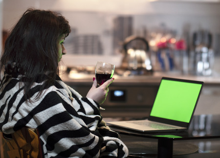 Woman sits with a glass of wine in the evening at home and looks at a laptop screen, chromakey