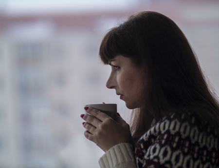 Young brunette woman drinks coffee and looks out the window thoughtfully