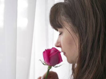 beautiful woman with pink rose near the window