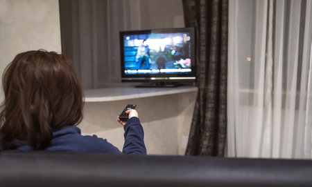 Woman switches tv channels while sitting at home on the couch, rear view