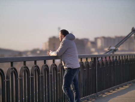 Young man stands alone on a bridge on a sunny day