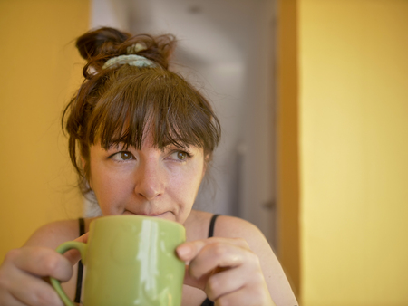 Sad and sleepy young woman with a cup of coffee in the morning at home Imagens