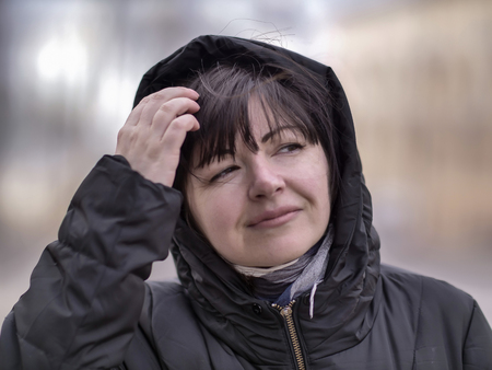 Portrait of an attractive woman in a black jacket with a hood against the background of the street