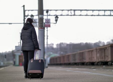 A lonely girl with a black suitcase is standing on the platform.