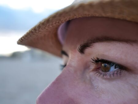 Portrait of a young woman in a hat looking to the side, close-up