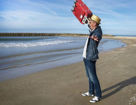 Positive young man happy standing on the seashore, raises a red suitcase up 写真素材