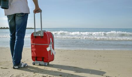 A tourist man in jeans with a red suitcase stands near the sea, space for text. 写真素材