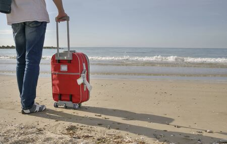A traveler in jeans with a red suitcase stands near the sea 写真素材