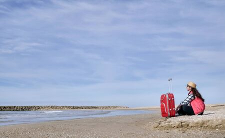 Attractive brunette travel girl sitting on the sand next to a red suitcase by the sea, against the blue sky, place for text Banco de Imagens
