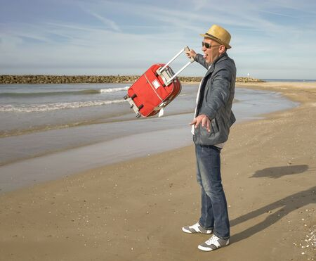 Happy male tourist rejoices standing by the sea, raises a red suitcase up
