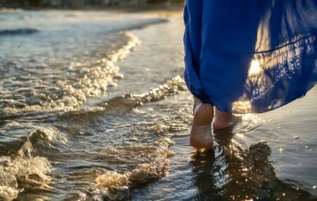 Feet of a girl in a skirt goes along the waves, glare of the sun on the water during sunset Archivio Fotografico - 129922407
