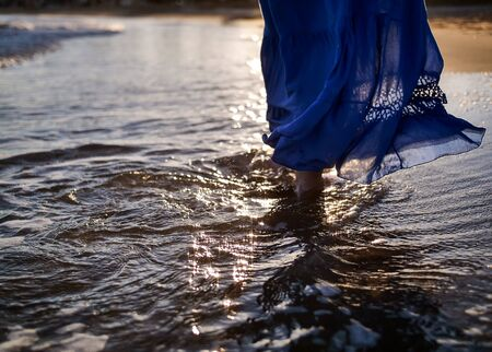 A young woman in a blue long skirt walks along the beach, the glare of the sun on the waves Archivio Fotografico - 129922424