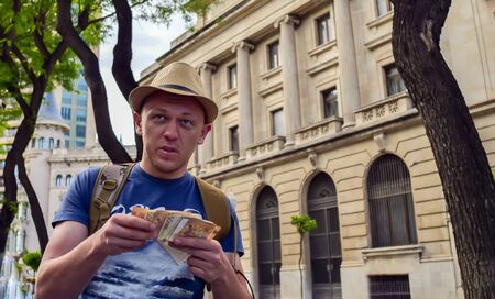 Attractive male tourist counts cash on the street of a European city