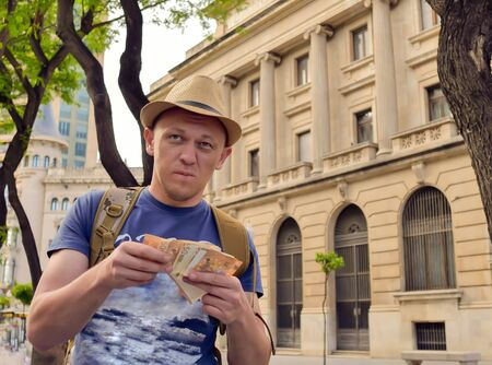 Male tourist holding cash on a street of a European city 스톡 콘텐츠