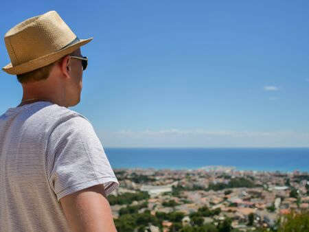 A man in a hat looks in front of him at a beautiful view of a settlement by the sea, close-up 版權商用圖片