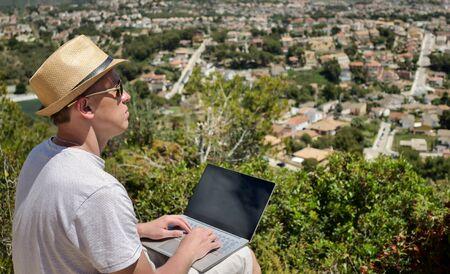 Freelancer guy working on the street, sitting on a mountain, enjoying the beautiful scenery around him, free work