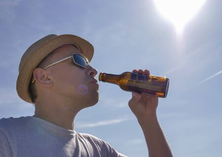 Attractive man in a hat drinks refreshing and cool beer from a bottle outdoors against a blue sky Stockfoto