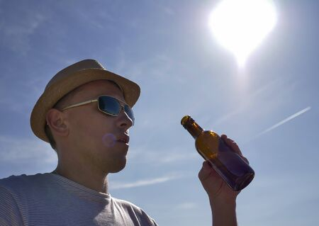 Young man in hat and glasses wants to drink refreshing and cool beer from a bottle outdoors