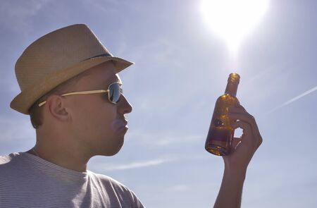 Attractive young man in hat and glasses examines a brown bottle with a drink, outdoors against a blue sky