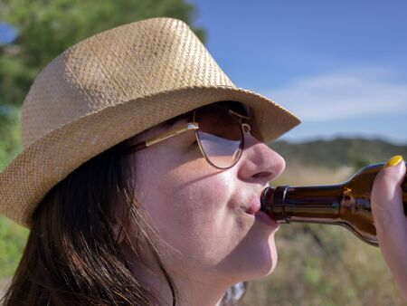 Close-up brunette girl in hat and glasses drinks a drink from the neck of a brown bottle Stockfoto