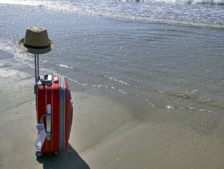A travel suitcase with a hat stands on the beach near the sea. Weekend concept