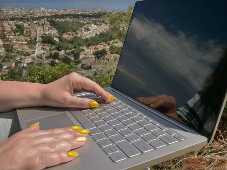 Female hands prints on a laptop, reflection in the monitor, against the background of nature Stock Photo
