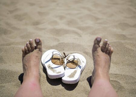 White slippers and sunglasses next to female legs on the beach, relaxation concept