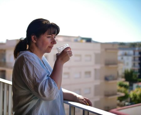 Young woman drinks from a glass while standing on a balcony against the background of the city