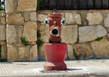 Old red fire hydrant on the street, looks like a face, funny face