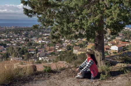 A brunette girl with a laptop sits under a tree on the background of a small town by the sea Stock fotó
