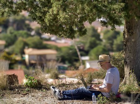 Attractive guy with a laptop and in a hat sits under a tree on a blurry background of a small town Stockfoto - 132329535