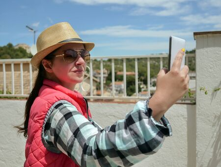 Young attractive brunette in a hat takes a selfie from her white mobile phone