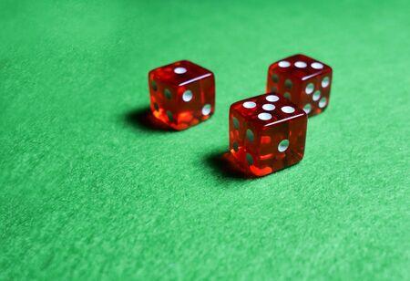 Tres dados rojos sobre tela verde, concepto de juegos de casino