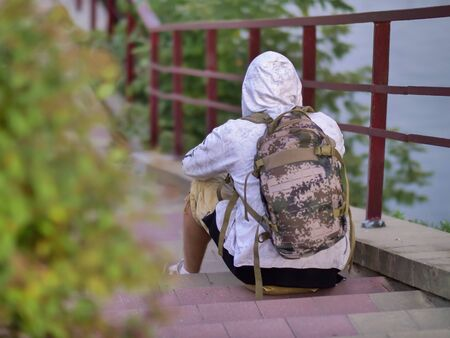 Lonely guy with a backpack and a hood sits on the steps of the stairs in the park Stok Fotoğraf