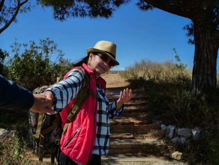 Girl tourist in a hat and with a backpack calls to follow her along the trail Stock Photo - 135079910