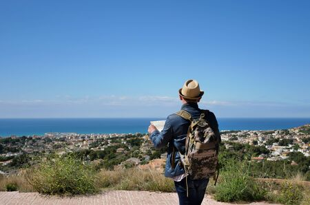 A young man with a backpack and a map of the area in his hands stands on a mountain near the city and the sea, rear view